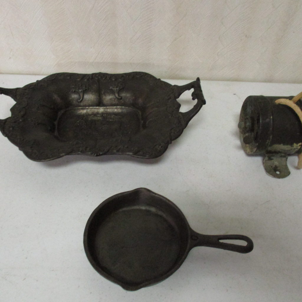 "Lot 136: Cast Iron Dish, ""0"" Griswold Skillet And Old Wash Line Reel"